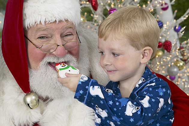 Young Boy in Pyjamas Feeds Father Christmas a Snowman Cookie